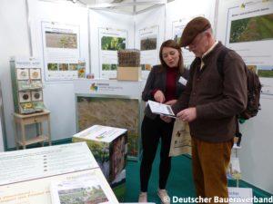 """Besucher der Agritechnica informiert sich mit dem Maßnahmenbuch über Naturschutzmaßnahmen im Projekt """"Lebendige Agrarlandschaften"""""""